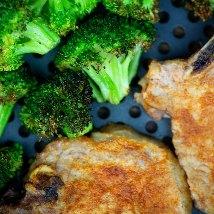cooked broccoli and pork chops in an air fryer pan