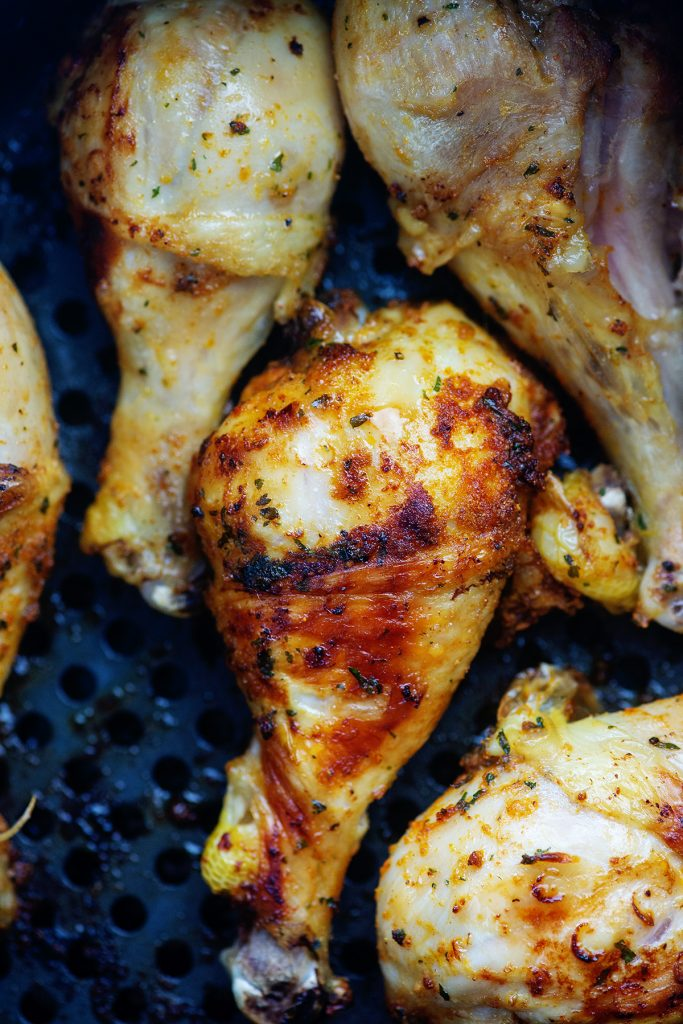 A close up of air fried chicken legs in an air fryer basket.