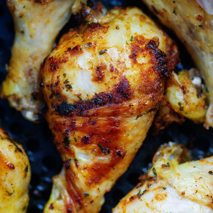 A close up of chicken drumsticks close together in a an air fryer pan.