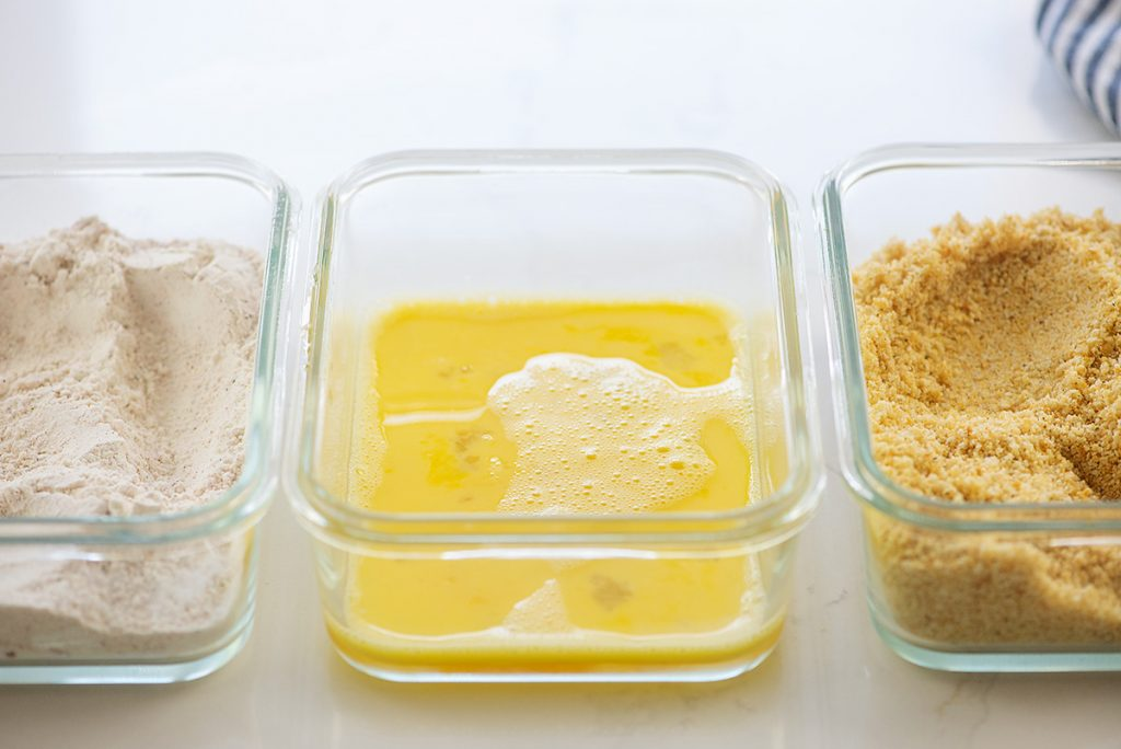 Three clear glass dishes of breading ingredients.