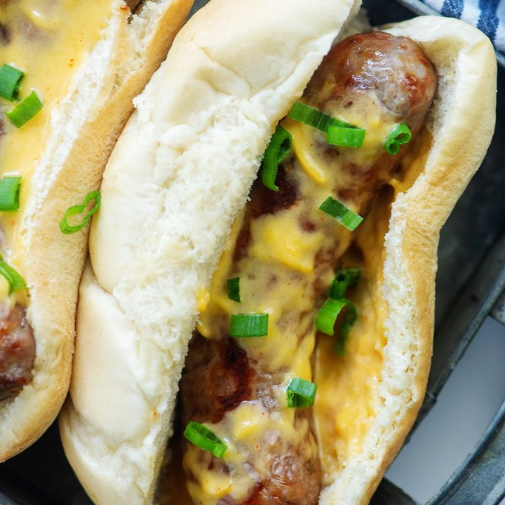 Overhead view of a cheesy brat topped with green onions.