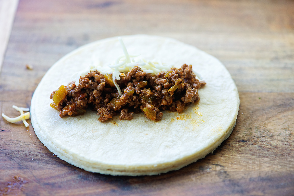 A flat tortilla with cooked ground beef and shredded cheese on it.