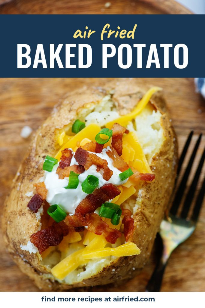 An overhead view of a loaded baked potato on a wooden cutting board.
