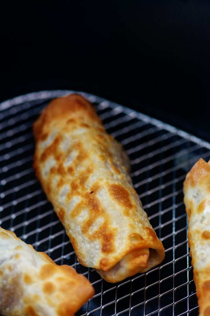 A close up of an egg roll in an air fryer basket