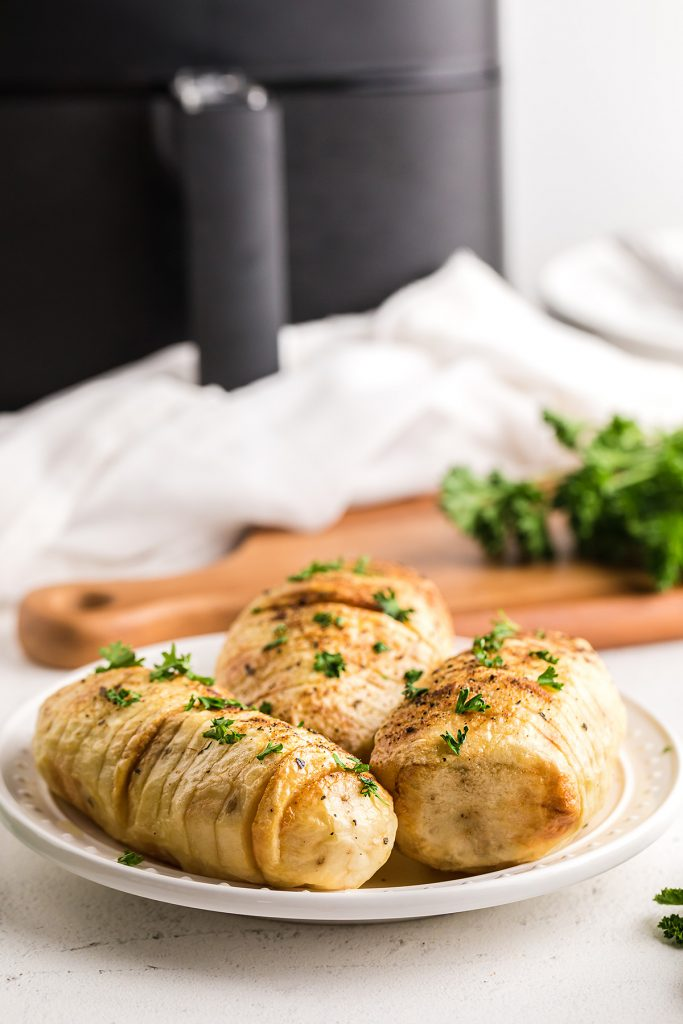 Three hasselback garlic potatoes garnished on a white plate