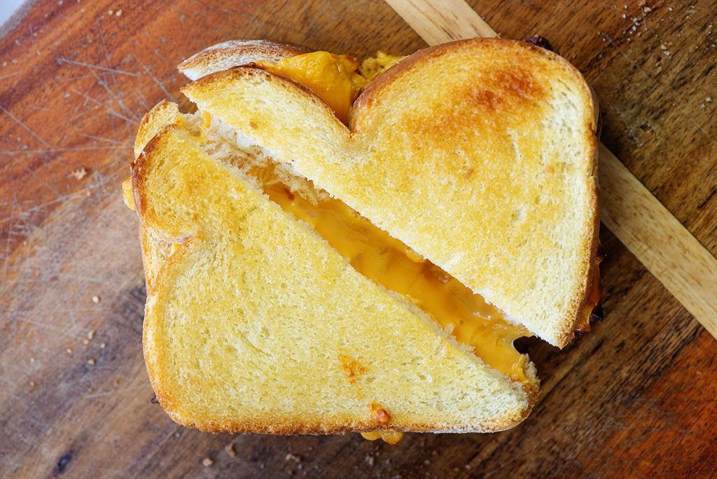 cheesy grilled cheese sandwich on wooden cutting board