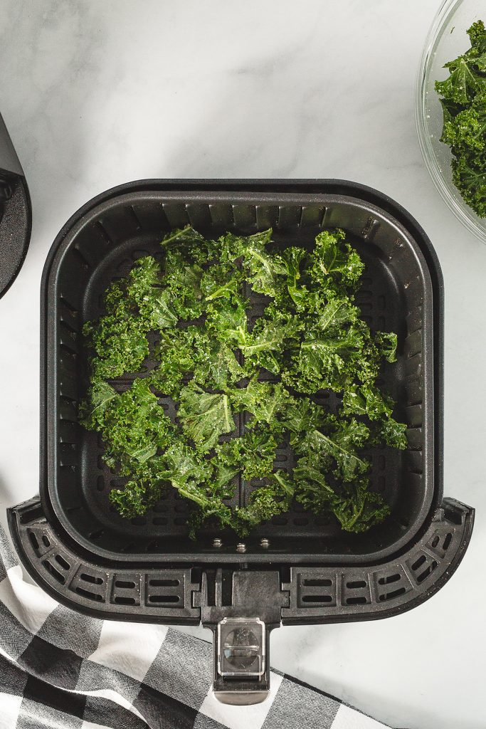 Overhead view of kale chips in an air fryer basket