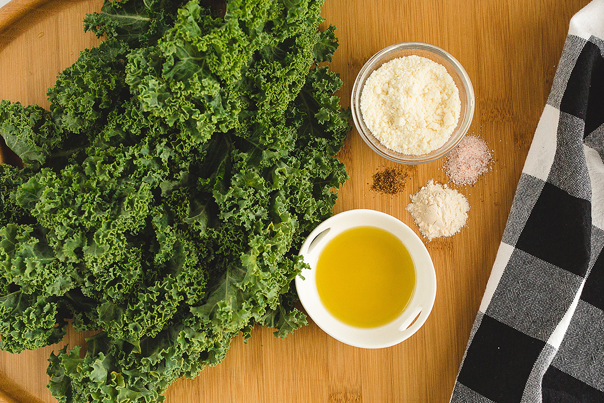 Kale chip ingredients on a wooden cutting board.