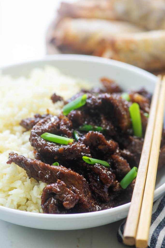 Mongolian beef on a white plate with chopsticks