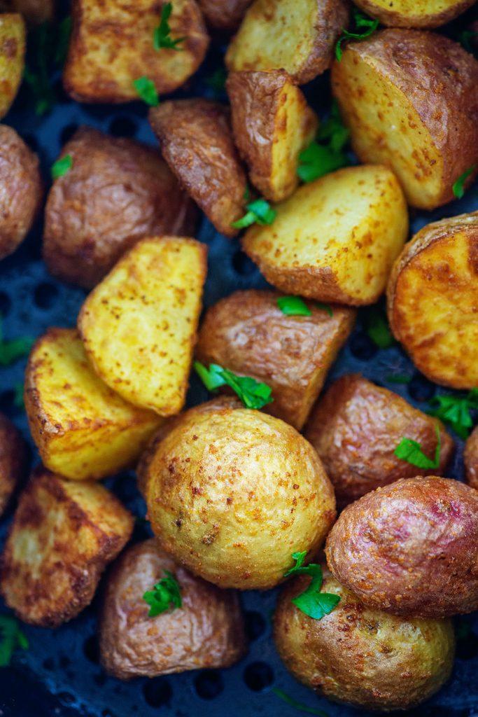 Cooked garlic butter potatoes in an air fryer basket.