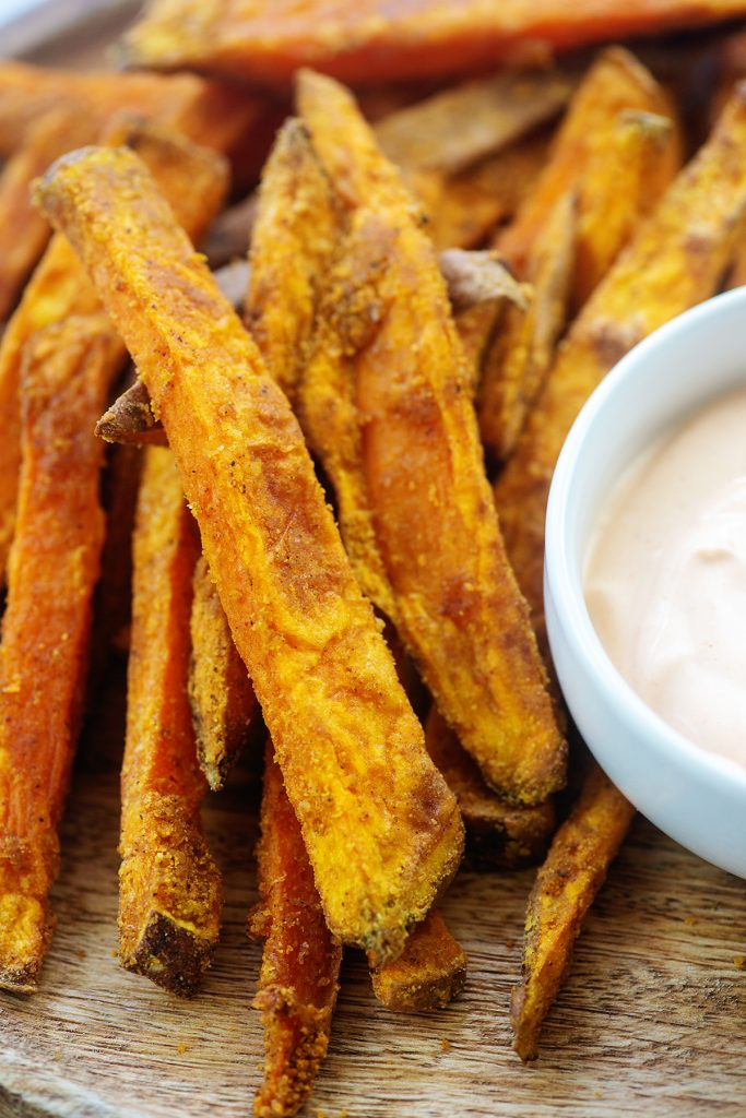 A close up of sweet potato fries on a wooden cutting board next to a bowl of dip.