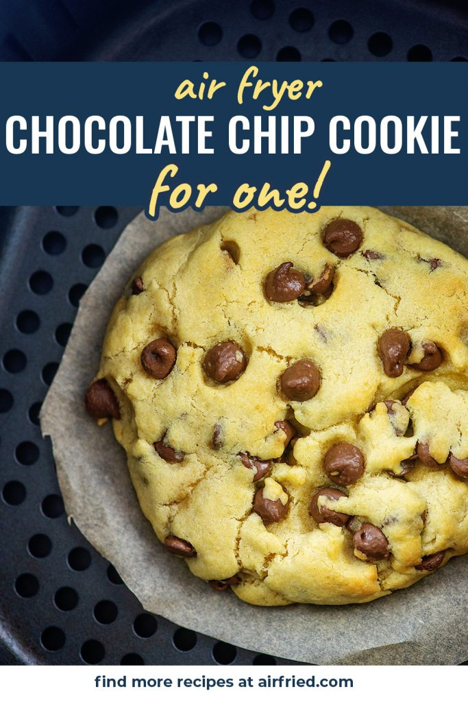 A big chocolate chip cookie in an air fryer basket.