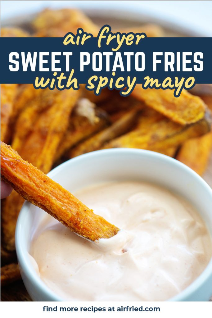 A sweet potato fry being dipped into a spicy sauce in front of a pile of fries.