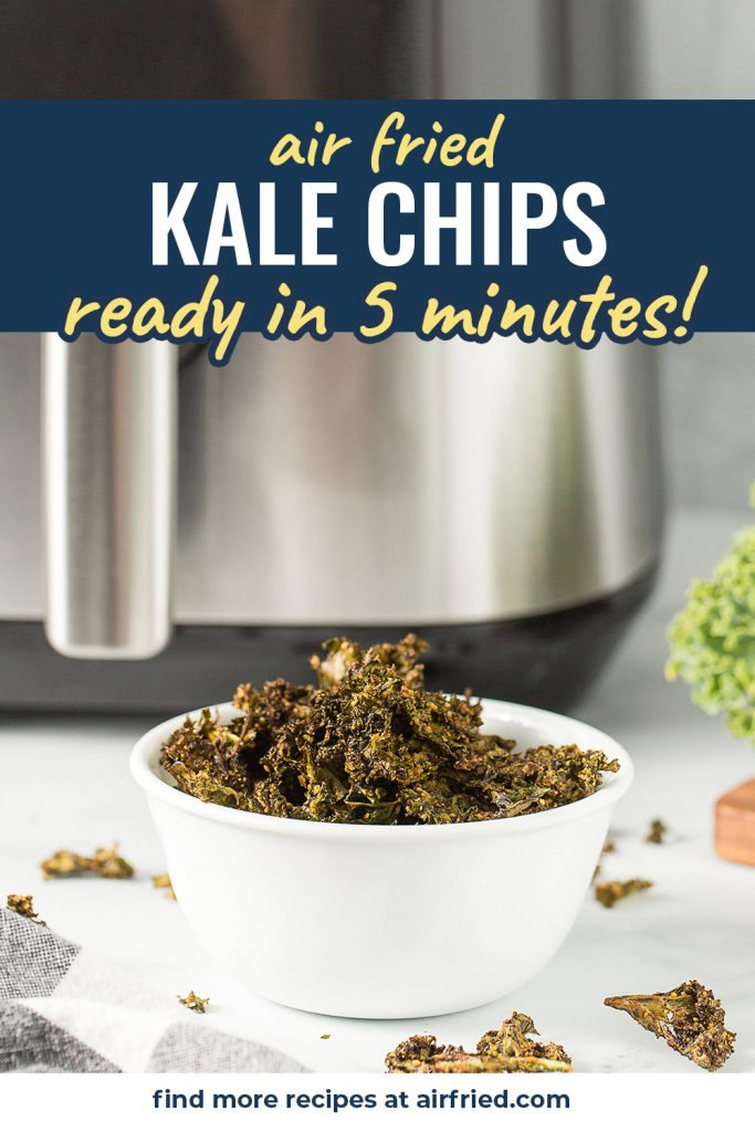Kale chips in a white bowl in front of an air fryer.