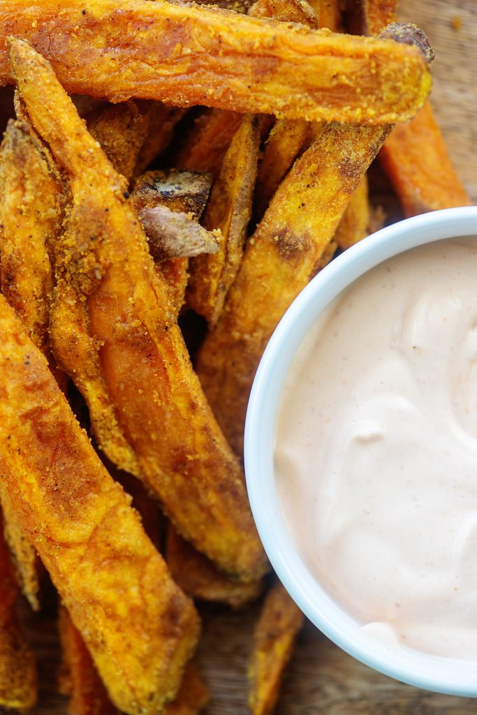 Overhead view of sweet potato fries next to a cup of dipping sauce.