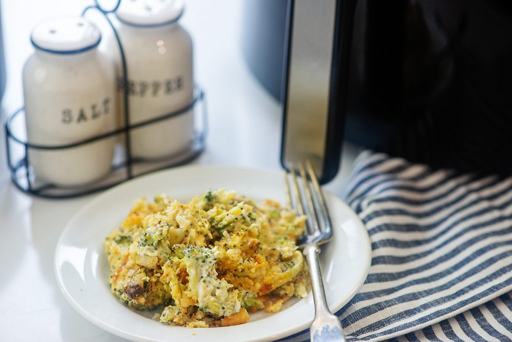 Cheesy broccoli casserole on a white plate in front of an air fryer