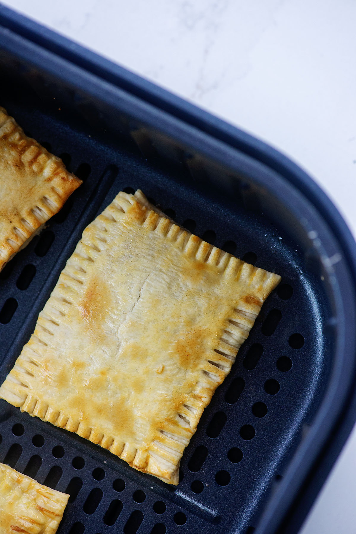A close up of a cooked pop tart in an air fryer basket