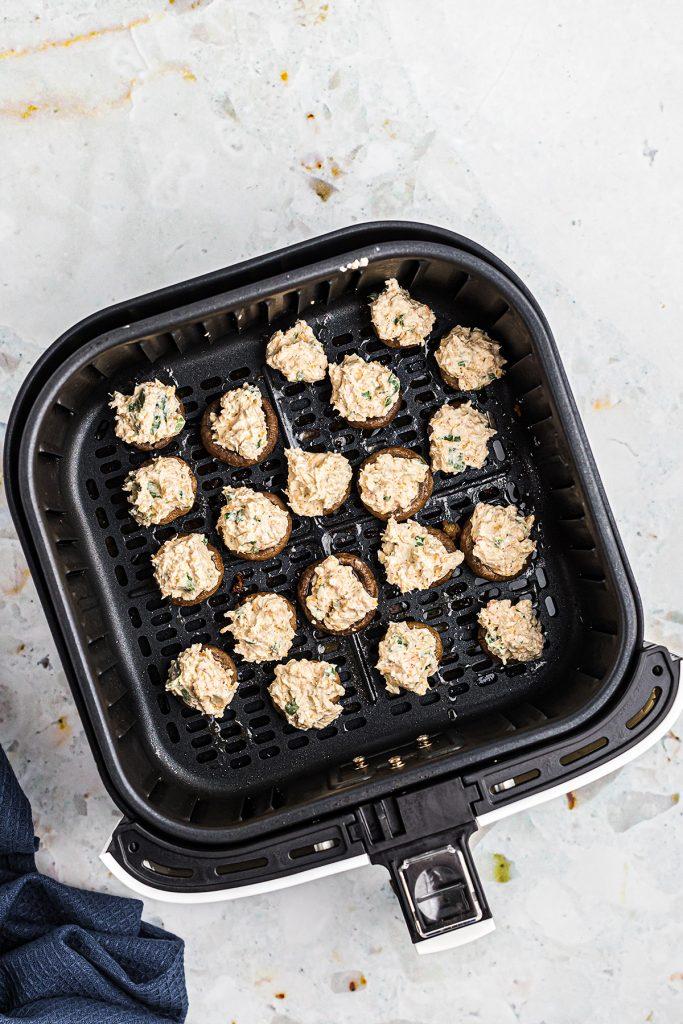 stuffed mushrooms being cooked in an air fryer basket