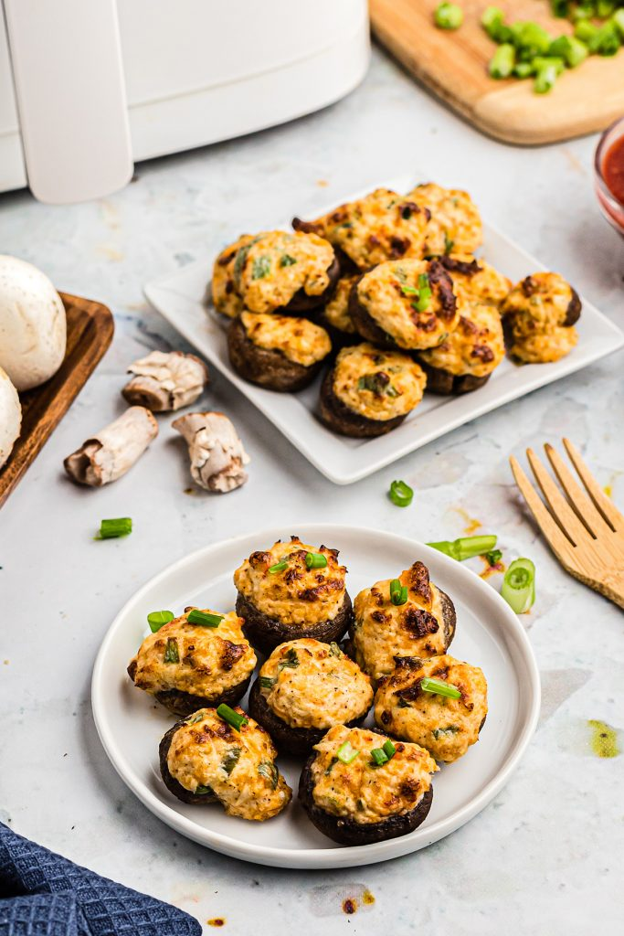two white plates with stuffed mushrooms piled up on them