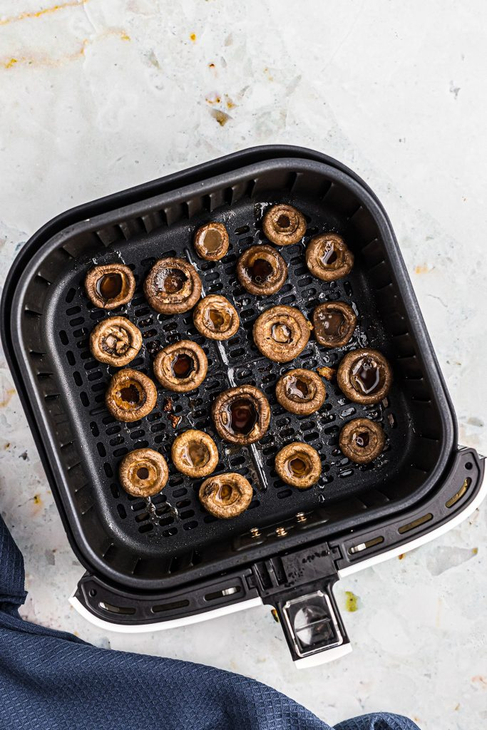 overhead view of cooked mushrooms in an air fryer basket