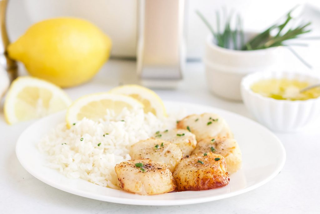 Sliced lemons on a plate with rice and scallops