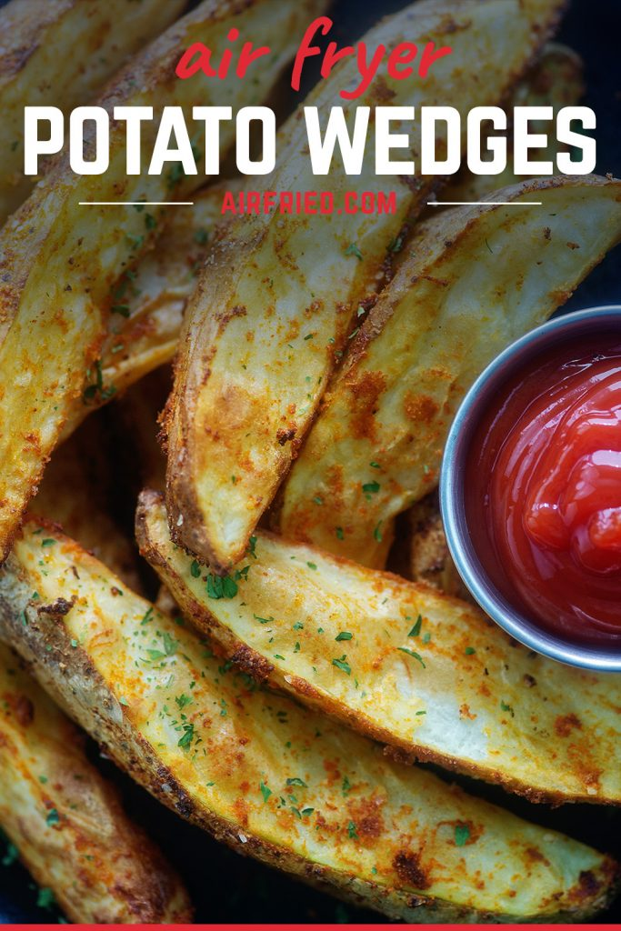 A close up of seasoned potato wedges next to a cup of ketchup