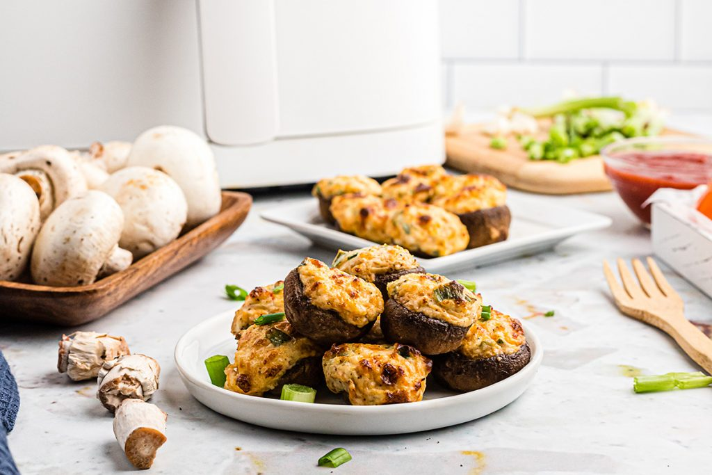 mushrooms on a plate in front of an air fryer