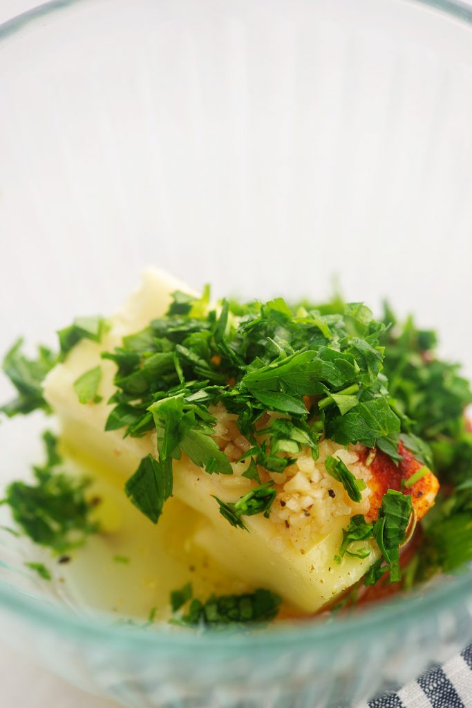 Butter and herbs in a clear glass bowl