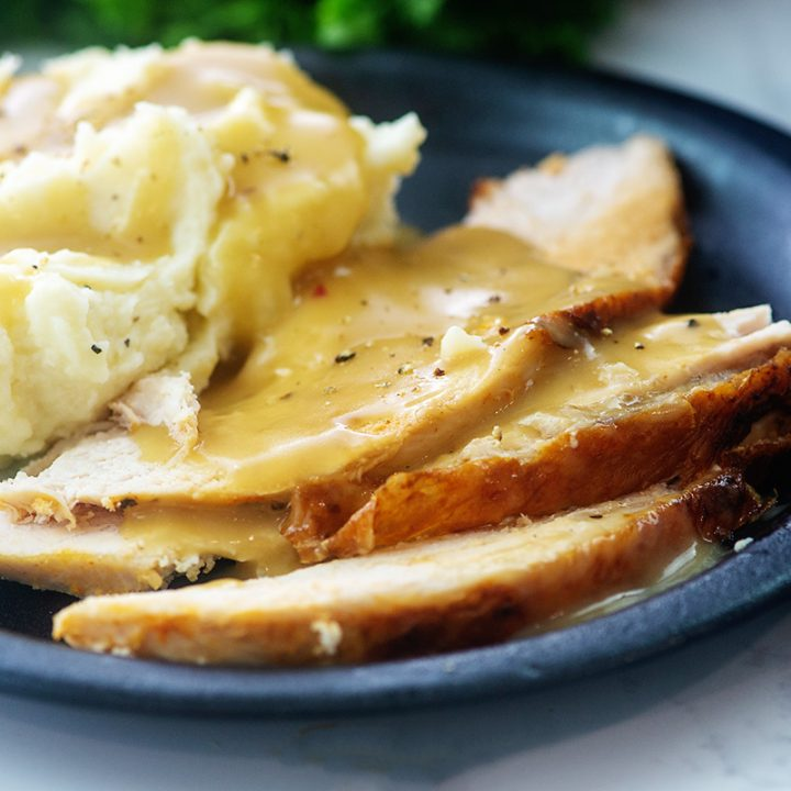 Mashed potatoes and gravy on a plate with turkey breast.