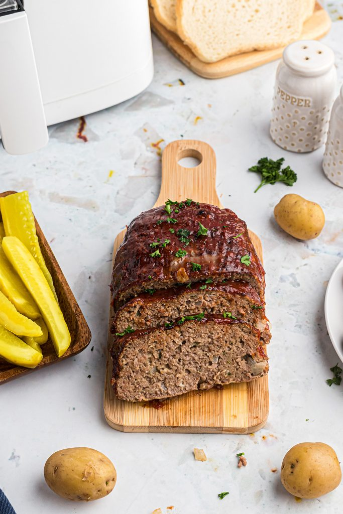 A meatloaf partially sliced on a small cutting board
