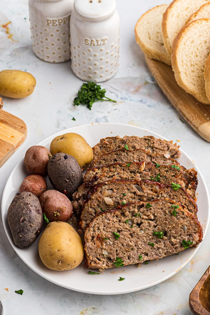 Sliced meatloaf and potatoes on a white plate in front of a salt and pepper shaker