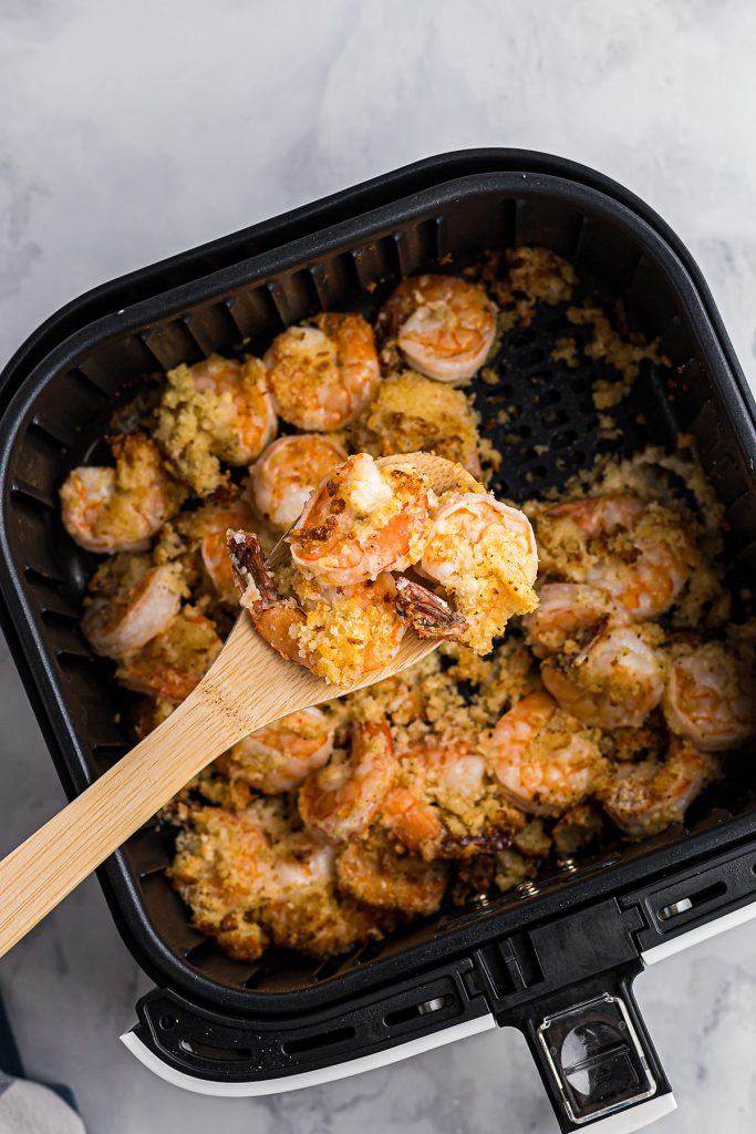 A wooden spoon scooping shrimp out of an air fryer basket