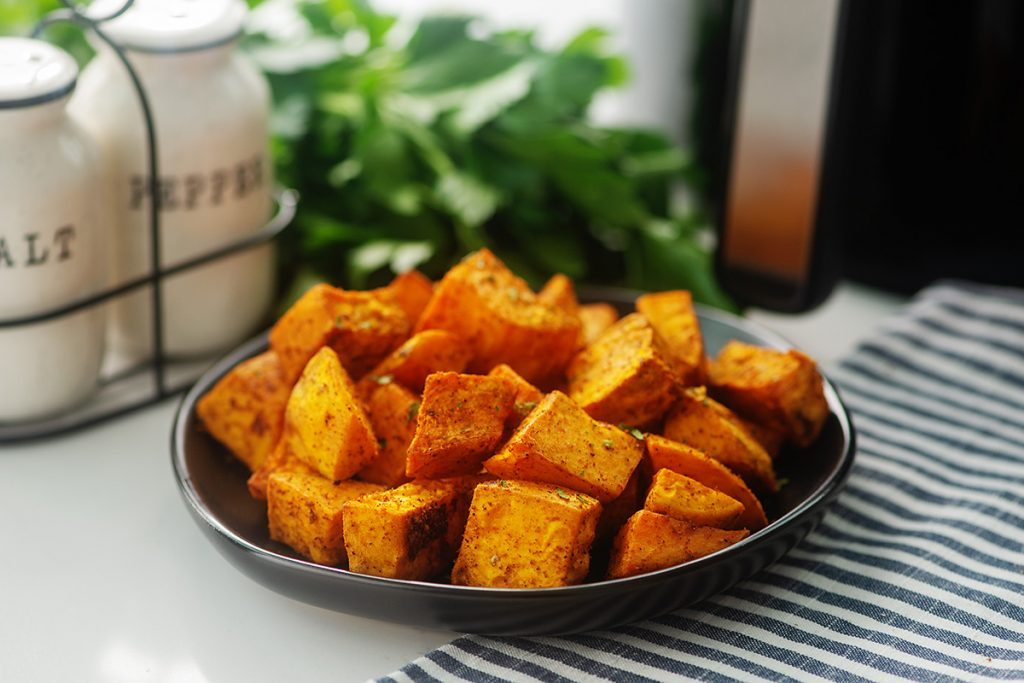 sweet potato cubes on a plate in front of salt and pepper shakers