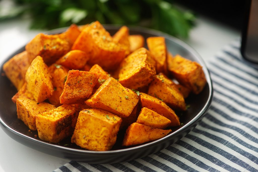 close up of sweet potato cubes on a black plate next to an air fryer