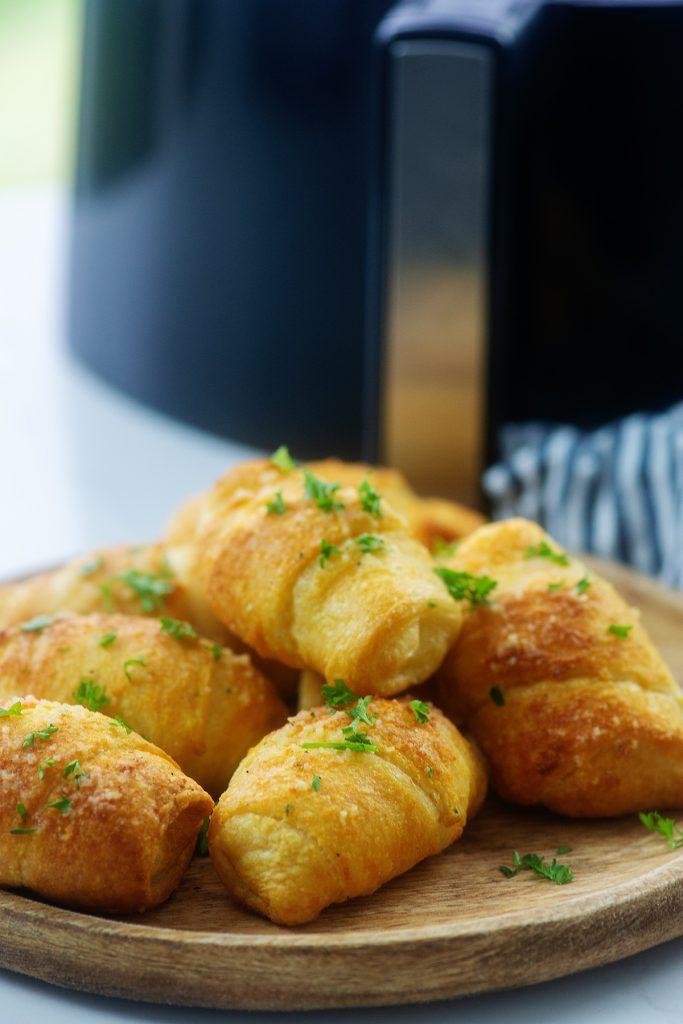 cheesy garlic crescent rolls on cutting board.