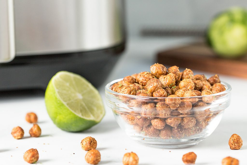A lime cut in half next to a bowl of chickpeas