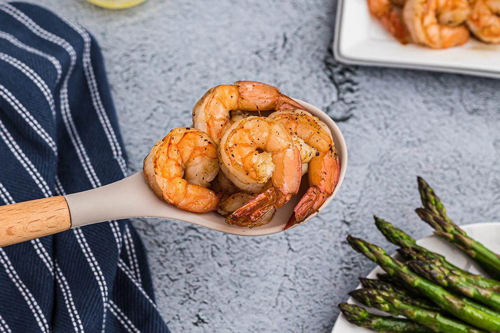 A large spoon of shrimp being held up to a camera.