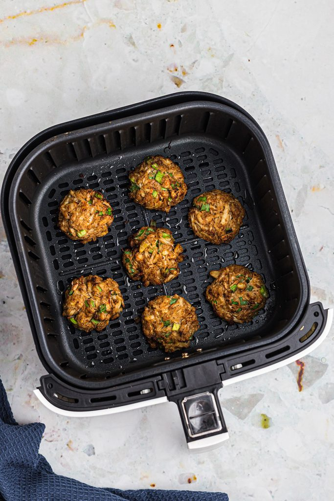 OVerhead view of 7 crab cakes cooked in an air fryer basket.