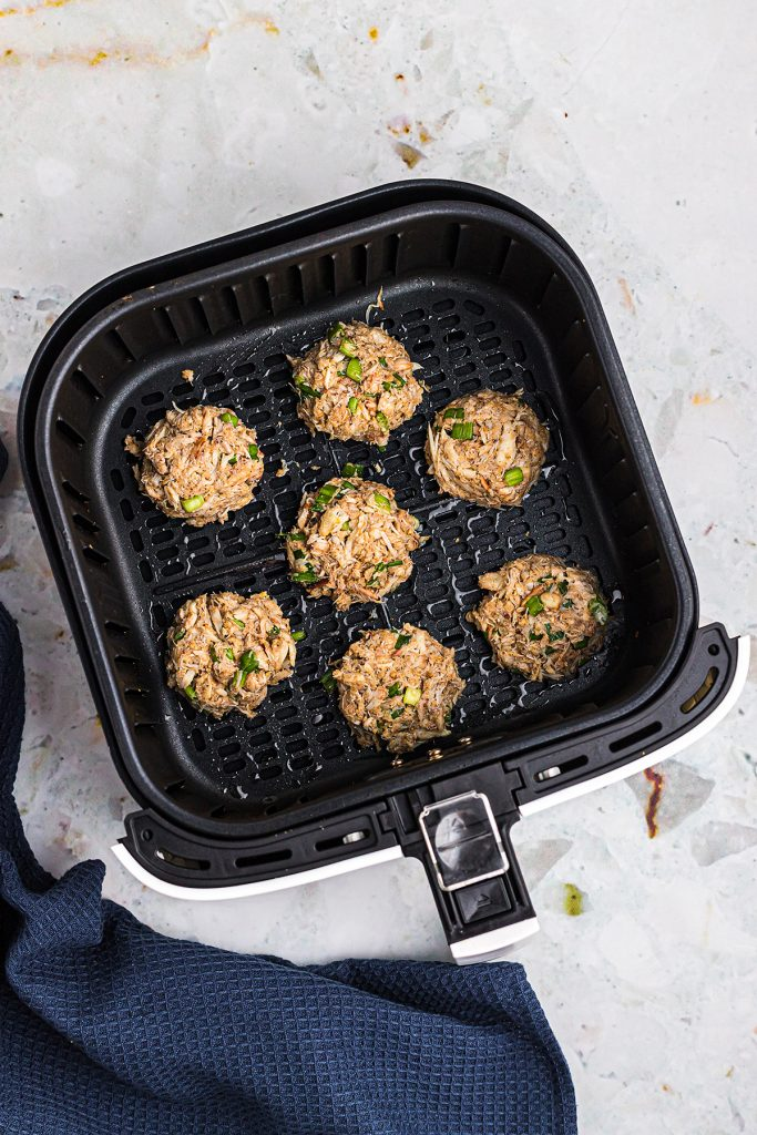 Overhead view of crab cakes in an air fryer basket