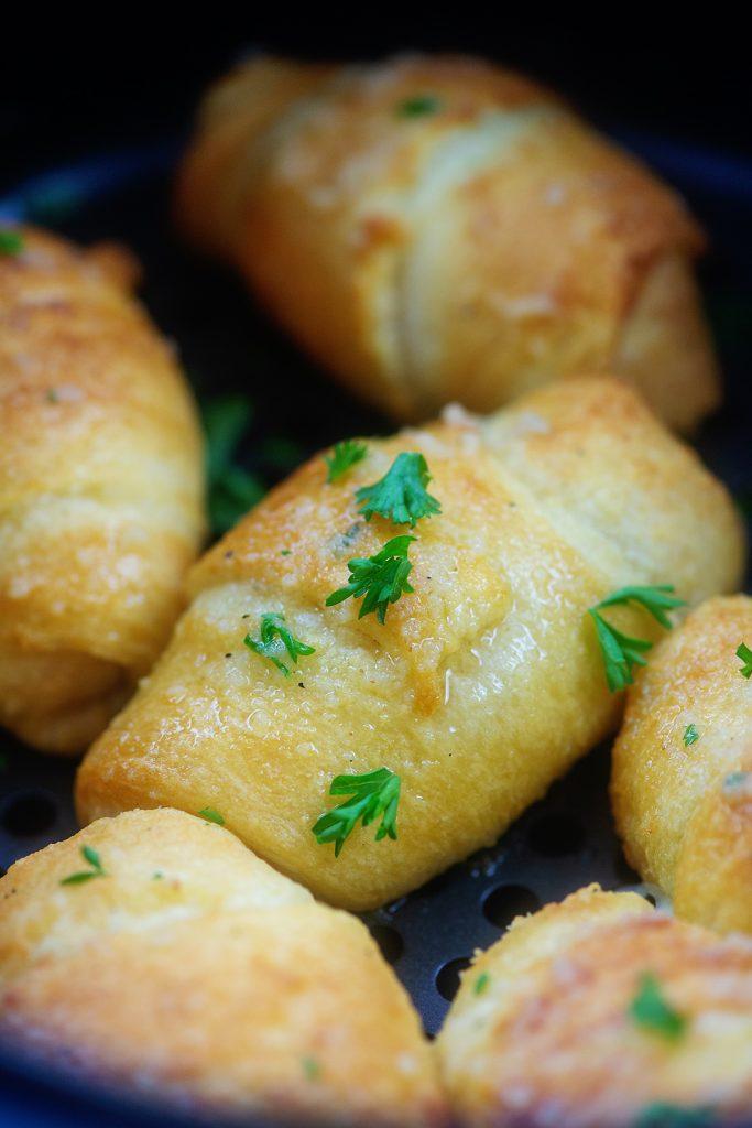 garlic butter crescent bombs in air fryer basket.