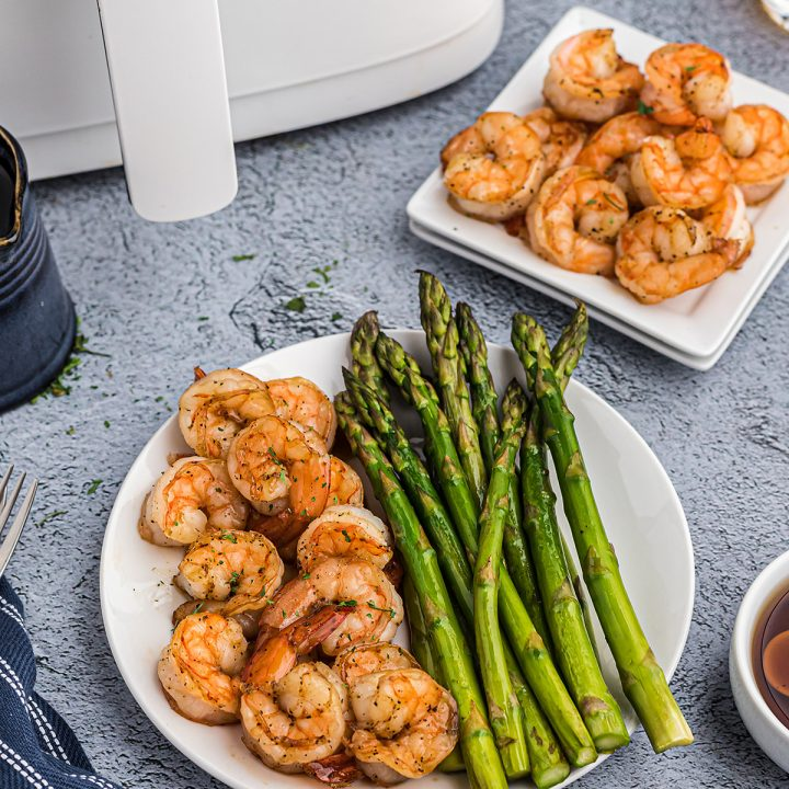 Two plates of shrimp in front of a white air fryer