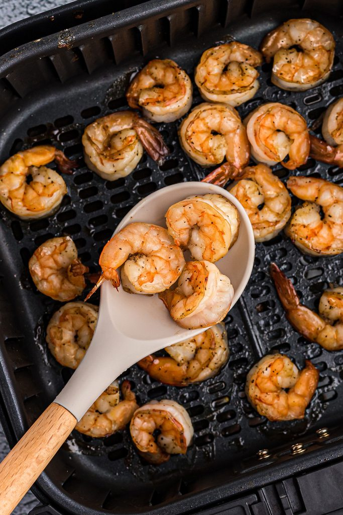 Cooked shrimp being scooped out of an air fryer basket.