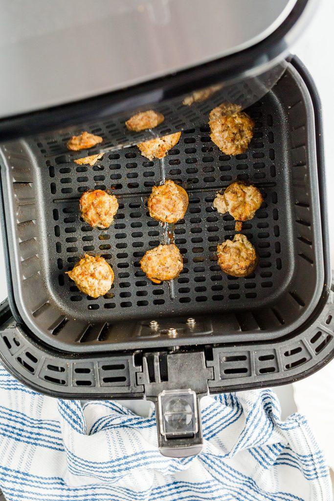 Overhead viewof stuffed mushrooms spread out in an air fryer basket.