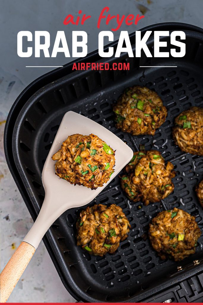 A spatula scooping a crab cake out of an air fryer basket