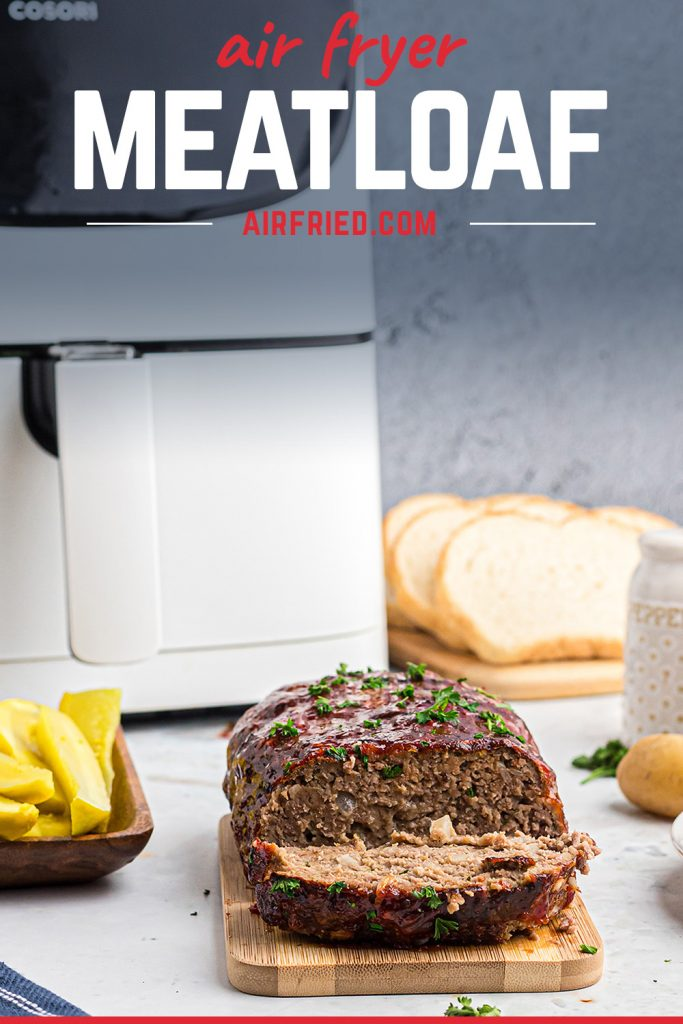 A meatloaf in front of an air fryer with a slice cut out of it.