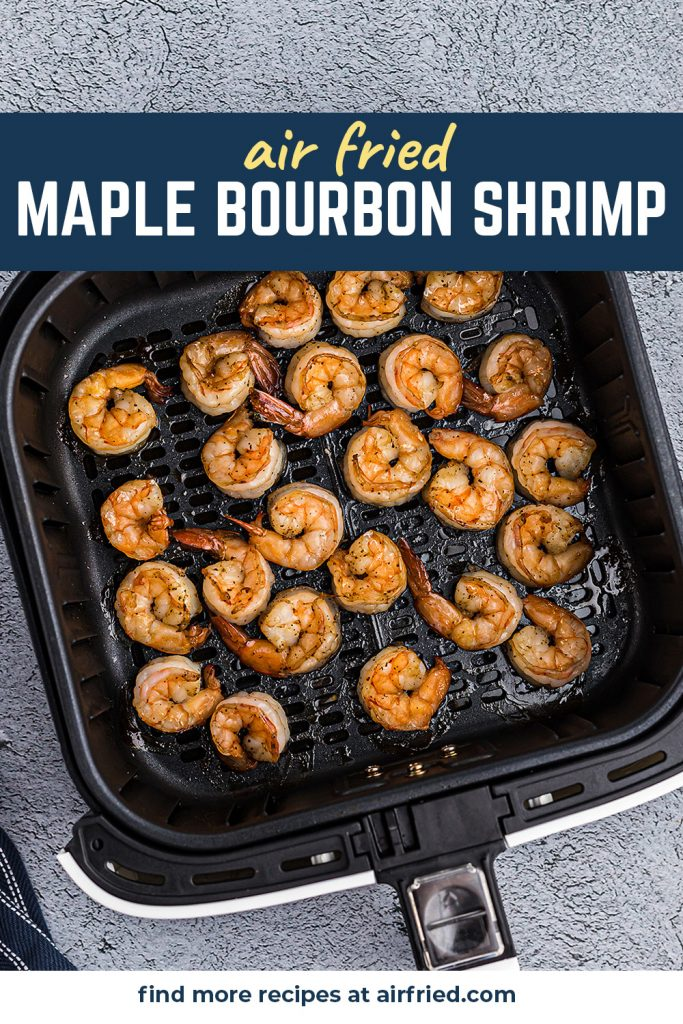 Cooked shrimp spread out in an air fryer basket with a maple bourbon glaze.
