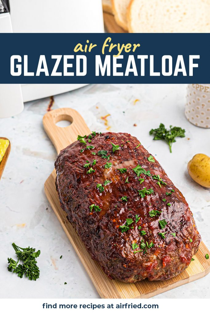 A glazed meatloaf on a small cutting board.