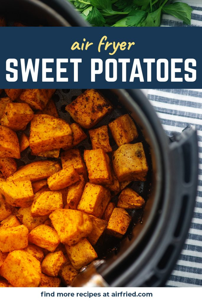 Overhead view of sweet potato cubes in an air fryer basket on a striped cloth napkin.