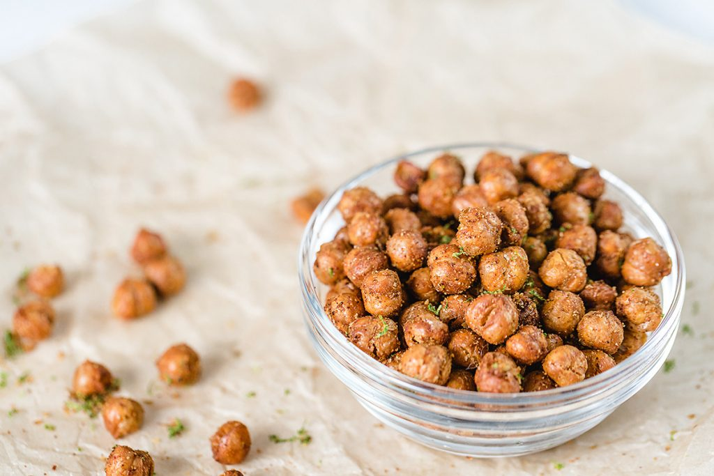chickpeas spilling out of a clear glass bowl