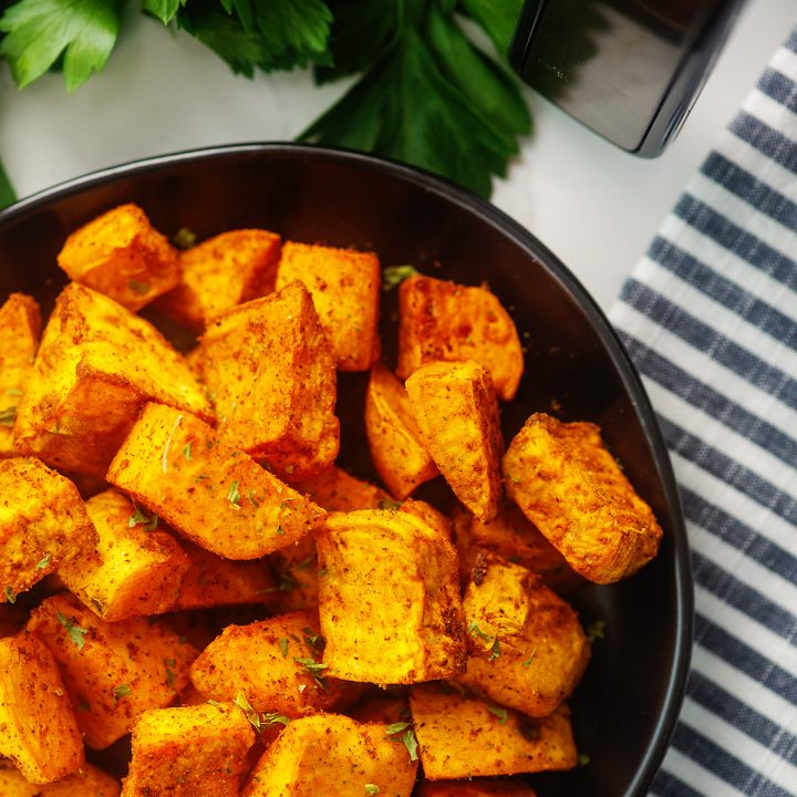 Overhead view of seasoned sweet potato cubes on a black plate.